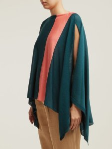 Woman wearing knitted cape with open sleeves and boat neck in teal shade, with contrasting stripe of peach running vertically across one side of garment.