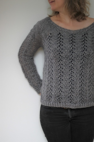 Woman wearing grey, wide scoop neck knitted sweater, with lace columns running vertically across body and sleeves.