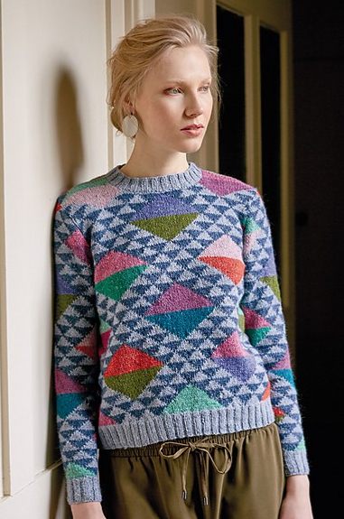 Woman wearing knitted jumper with all-over, triangle intarsia design in many colours.