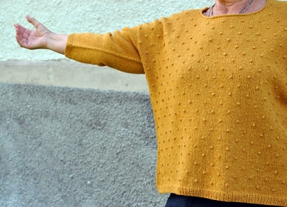 Woman, with arm outstretched, wearing mustard yellow, knitted sweater with all-over bobble texture.