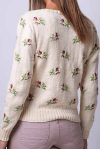 Woman wearing knitted white, fitted cardigan with floral intarsia motifs in red and green repeated across the fabric.