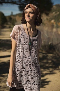 Model wearing tunic length, knitted linen top with all-over lace design, in soft pink.