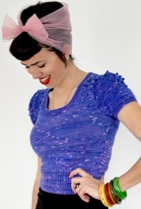 Woman wearing fitted, knitted top with bobble detail at shoulders and deep rib at hem. Styled with multicoloured bangles and tulle head scarf.
