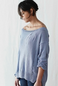 Woman wearing pale blue, knitted sweater with faux rips made of dropped stitches.
