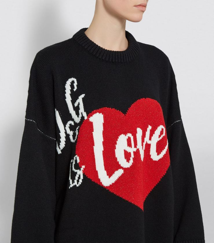 Model wearing knitted, black sweater with 'D&G is love' slogan formed in intarsia colour-work in white and red.