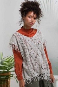 Woman wearing knitted, oversized top with openwork lace and fringe at end of short sleeves and hem.