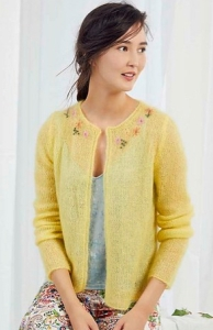 Model wearing mohair, knitted cardigan in warm yellow, with multicoloured, floral embroidery detail at neckline.