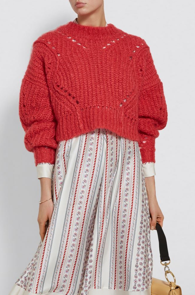 Model wearing a knitted, oversized, cropped red sweater with curving lines of eyelets and voluminous sleeves.