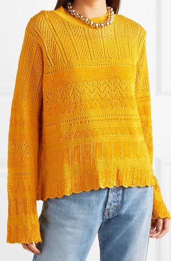 Model wearing yellow sweater with all-over lace panel details and flared sleeves. From McQ Alexander McQueen.
