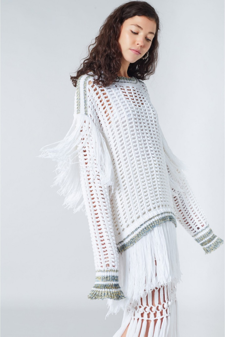 Model wearing Sonia Rykiel White knitted, oversized, white dress with allover mesh and fringe detail at back and hem.