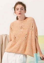 Woman wearing chunky, cotton knitted sweater in pale orange, with distressed effect created by faux holes and rips formed by lace stitches.