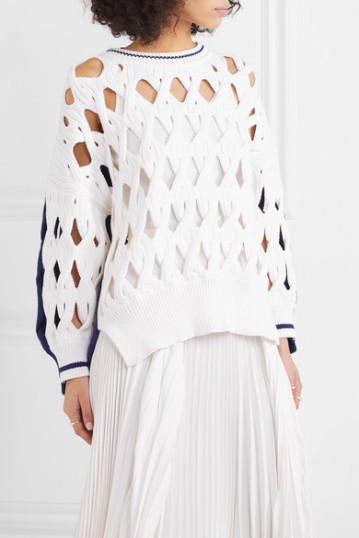 Model wearing oversized, white sweater with contrasting blue stripes on sleeve and collar, and with all-over, large, open mesh detail created with twisted, macrame
