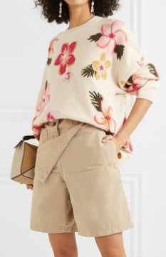 Model wearing oversized, cream sweater with multicoloured floral intarsia design; sweater worn tucked in to stone coloured shorts.