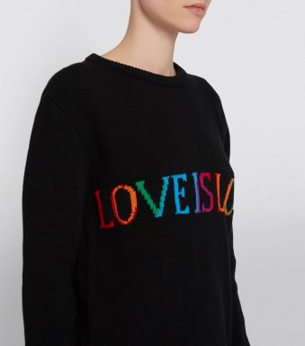 Model wearing knitted wool cashmere sweater in black, with contrast, multicoloured slogan formed in intarsia across the chest, which says 'Love is love'.
