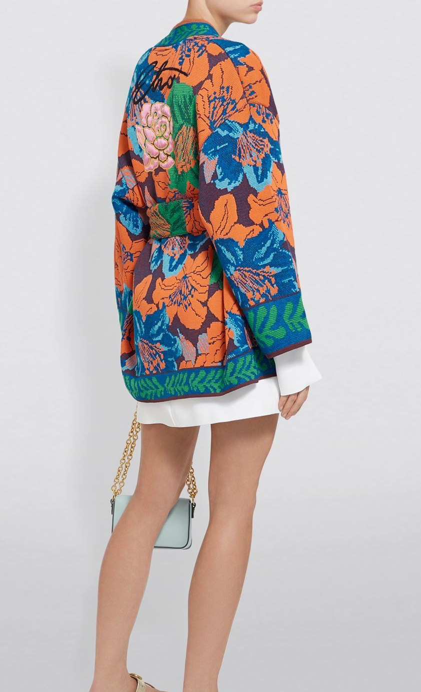 Model wearing long, wool blend cardigan with all-over, richly decorative, floral intarsia colour-work In oranges, blues and greens, and with contrast hem and cuffs.