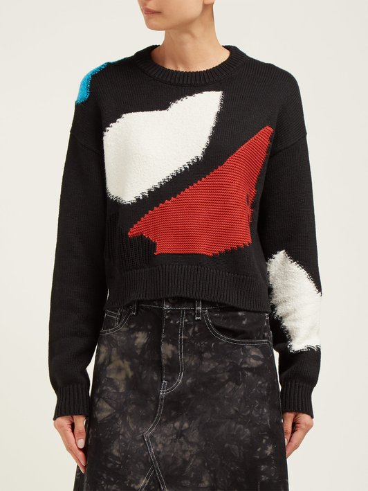 Woman wearing black sweater with geometric intarsia shapes in red, white and blue that give impression of patches.