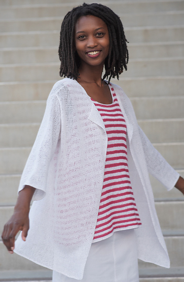 Woman wearing red/white striped top with a white skirt and a long, sheer, knitted cardigan made from white linen.