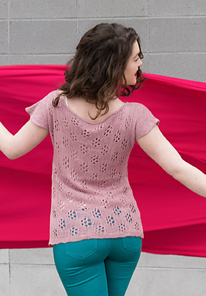 Woman wearing dusky pink, rayon/linen, knitted top with short sleeves and all over lace motif across back.