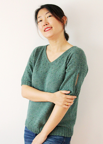 Woman wearing sage green, knitted top made out of wool/cotton blend; the top has a v-neck, and eyelet lace detail at the top section and hem, plus cut-out sleeve detail.