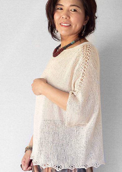 Woman wearing oversized, cream, cotton sweater with dolman sleeves and eyelet lace detail at shoulders.