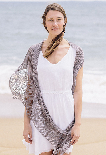 Woman standing on a beach. She is dressed in a white dress and wearing a knitted, grey shawl worked in brioche stitch and with a wide lace border.