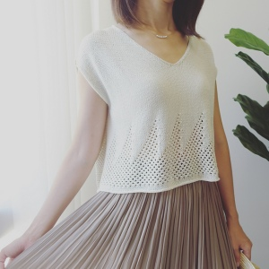 Woman wearing white, v-neck knitted cotton/rayon tee with v-neck and repeated triangle mesh lace motif around hem.