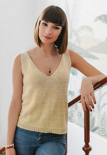 Woman wearing pale yellow, knitted tank top made out of cotton/linen blend, and with deep v-neck and rib detail at hem.