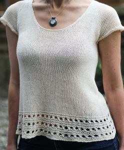 Woman wearing knitted, linen tee with short sleeves, scoop neck and eyelet border at hem.