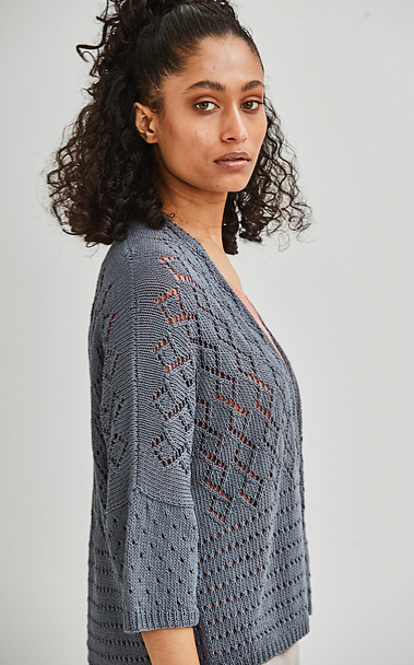Woman wearing slate grey knitted cardigan made out of linen and with all-over lace diamond and eyelet motifs.