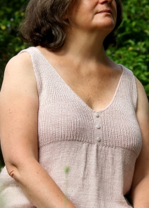 Woman wearing knitted v-neck tank top with rib bodice and button detail, made in wool/cotton.