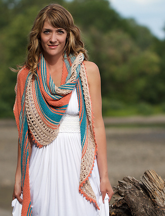 Woman wearing knitted, cotton/linen shawl in orange, blue and cream stripes of garter and lace.