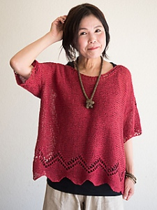 Woman wearing knitted, linen top with zigzag lace detail at hem.