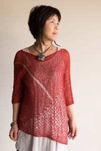 Woman wearing knitted, red sweater made from tencel fibre, with asymmetric hem and lace panel.