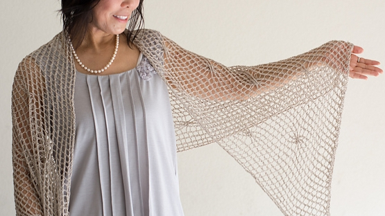 Woman wearing cream, knitted silk stole with all-over mesh texture and occasional twisted stitch that creates a small swirl in the fabric.