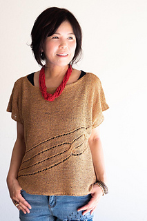Woman wearing wide scoop neck, knitted silk/cotton top with twisted cable details across front, defined in eyelet stitches.