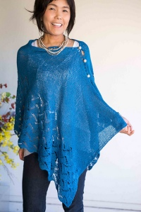 Woman wearing azure blue, knitted silk/cotton poncho, buttoned on one side at shoulder and with wide lace border.