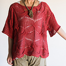 Woman wearing warm red, knitted linen top with wide scoop neck, elbow length sleeves and all-over, twisted stitch and dropped lace pattern.