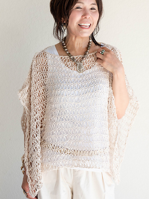 Woman wearing knitted, white poncho made in all-over, dropped stitch, open lace design.