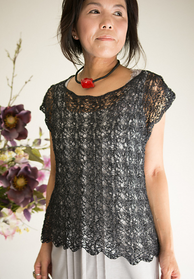 Woman wearing scoop neck, short sleeved top knitted in cotton and with delicate, all-over lace design.