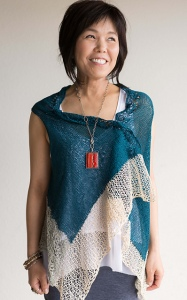 Woman wearing oversized, knitted, cotton vest in teal with cream lace border.