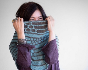 Woman wearing large, knitted cowl, pulled up over her face to show slip-stitch colour work design of curved sections of blue and grey colour.