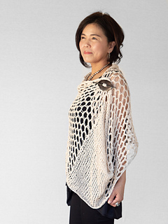 Woman wearing knitted, cotton wrap with panels of large lace eyelets, wrapped and secured at front using shawl pin.
