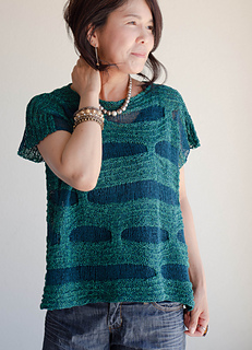 Woman wearing short sleeved top knitted in cotton, with contrasting strips of teal and blue.