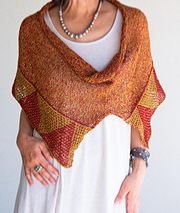 Woman wearing knitted cotton, burnt orange poncho or cowl with mosaic stitch triangle border in contrasting yellow.
