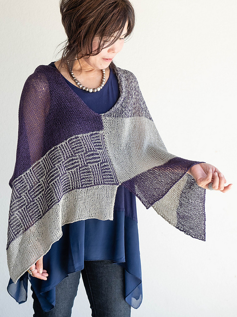 Woman wearing knitted, cotton poncho with patchwork panels of solid, marled and mosaic stitch geometric design.