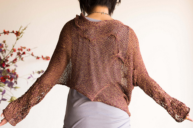 Woman showing the back of a knitted, cotton sweater with gentle, organic cable details across the back, asymmetric hem and lace detail from elbow to the cuffs that fall mid hand.